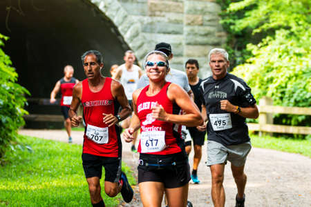 Babylon, New York, USA - 12 August 2018: Women smiling at camera after running our of a tunnel during the Dirty Sock 10K trail race. Imagens - 154487555