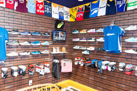 Smithtown, New York, USA - 28 August 2020: Running shoes are on display with clothing and uniform tops hanging on the wall at a local running shoe store. Editorial