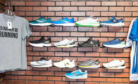 Smithtown, New York, USA - 28 August 2020: The wall of a running shoe specialty store has different brands of shoes displayed on the wall next to some t-shirts.