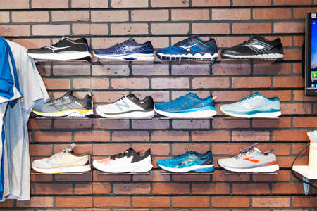 Smithtown, New York, USA - 28 August 2020: Running shoes are against the wall on display at a running shoe specialty store. Imagens - 154487552