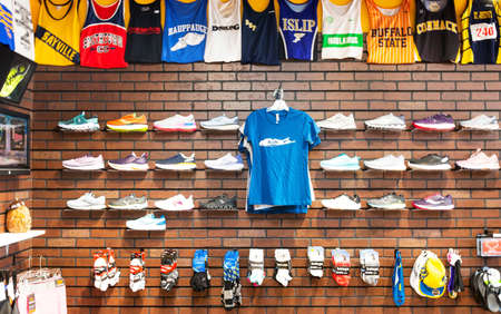 Smithtown, New York, USA - 28 August 2020: The inside of a running shoe store with rows of shoes and socks and local uniform tops hanging as decoration. Imagens - 154487551