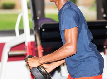 A cross country runner is holding a twenty five pound weight twisting side to side in a weightroom during practice.
