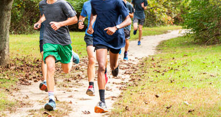Front view of a group of high school cross country runners running fast on a dirt path with leaves on the ground.