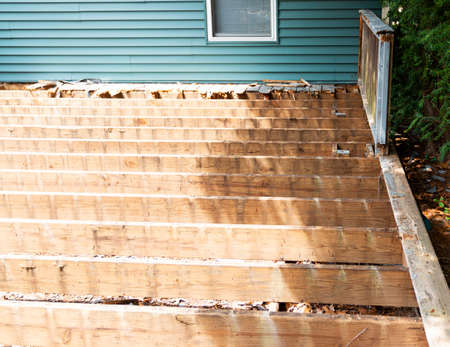 The old wood of a backyard deck has been removed to install composite material deck on top.
