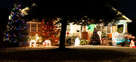The front of a house is light up with Christmas ights and decoratiions to celebrate the holiday.