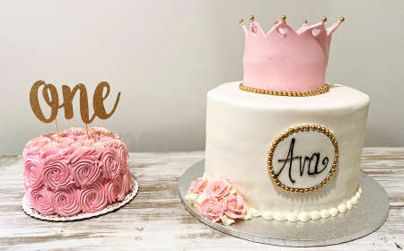 A pink smash cake and a white cake to eat on a table for a one year olds birthday celebration.
