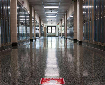 An empty high school hallway with one way sign taped on the floor as part of the neew normal for opening up schools in a pandemic.