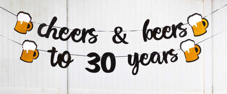 A 30th birthday party banner reads cheer and beers to 30 years woth beer mugs on either end.
