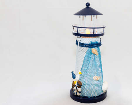 A blue and white small toy lighthouse used for table decoration with a nautical theme with a white background