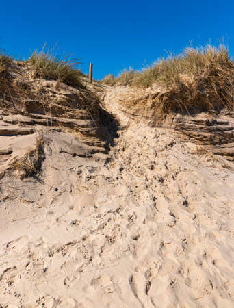 A sand dune on Montauk Beach not far from Montauk Point with footprints from those that have come and gone before me.