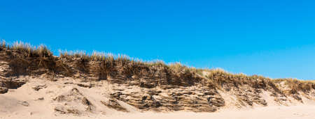 Horizontal picture of the dunes on Montauk Beach that have been eroded by the water of the Atlantic Ocean with a deep blue sky above. Imagens