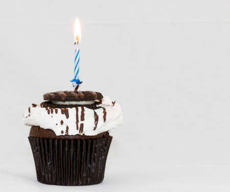 A birthday cupcake with a lit blue candle and a white background.