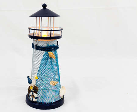 A small blue and white to lighthouse used as a table decoration with nautical thieme.