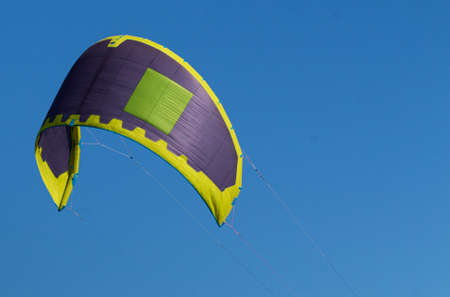 A purple, yellow and green sail of a Kite surfer in the air with a deep blue sky as its background. Imagens