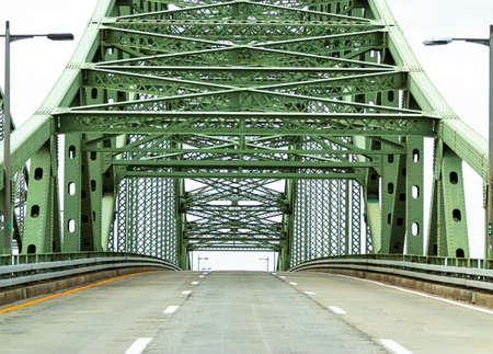 View of driving on a three lane highway up a bridge approaching its apex with no cars on the road travelling back from Fire Islnad to the mani land of Long Island New York.