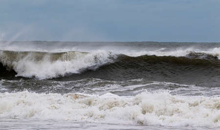 The Atlantic Ocean off the coast of Fire Island New York is very rough with many waves forming from a tropical storm and very strong winds blowing the water backwards.)