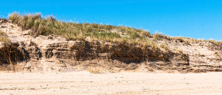 Horizontal view of a sand dune that has been battered by the Atlantic Ocean with a blue sky in Montauk New York.