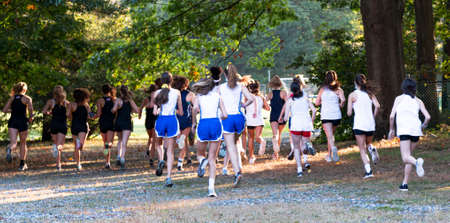 Rear view of the start of a girls running race on rocks and grass as they run nfor posittion.
