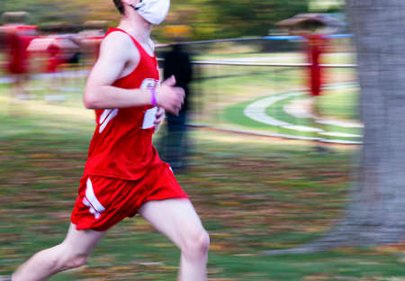 A high school cross country runner with a blurred background as he finishes a race wearing a face mask during the coronavirus COVID-19 Pandemic.