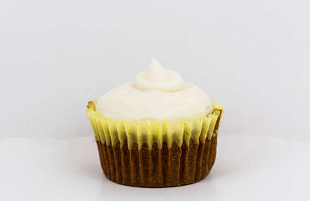 Carrot cake cupcake with cream cheese frosting and a white backgrond close up.