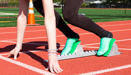 A high school girl is in the set position in a set of starting blocks on a red track with green spikes on.