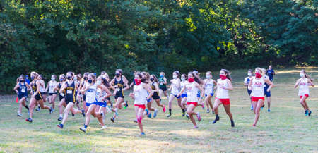 Syosset, New York, USA - 10 October 2020: First race of 2020 with high school girls running wearing face masks at the start of the cross country race on a grass field.