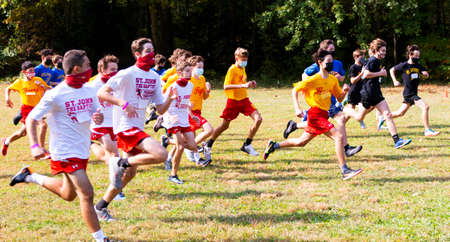 Syosset, New York, USA - 10 October 2020: The start of a boys Freshmen cross country race during the coronavirus pandemic with runners wearing masks. 新聞圖片