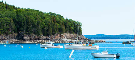 View looking at boats moored just off a rocky island in Bar Harbor Maine.