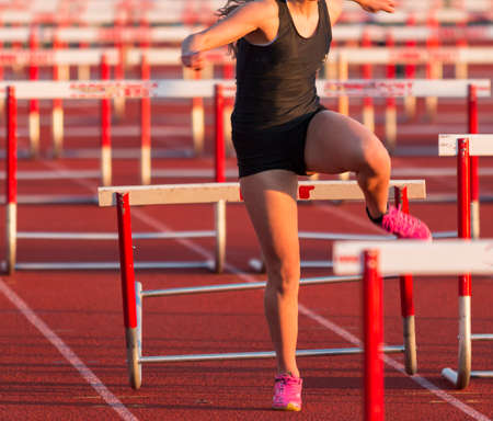 A high school girl running in a hurdles race hits and trips over one of the hurdles.