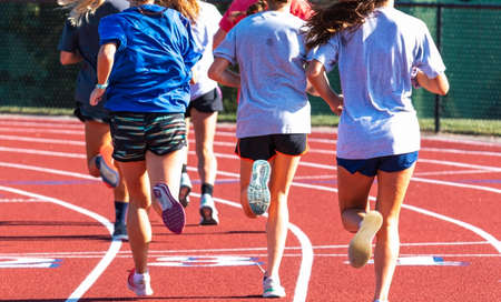 Rear view of a group of high school girls running on a track during practice.