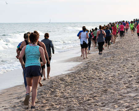 Rear view of hunreds of people running and walking along shore close to the water on a beach in Fire Island during a one mile race in the early evening in the summer.