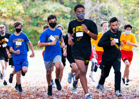 Syosset, New York, USA - 1 November 2020: High school freshmen cross country runners running a race wearing face masks with autumn leaves on the ground. 新聞圖片