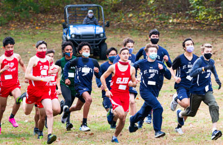 Syosset, New York, USA - 1 November 2020: Start of Hhgh school boys cross country running race with boys wearing face masks and gaiters and a golf cart in background ready to follow them. 新聞圖片