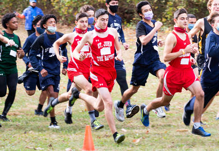 Syosset, New York, USA - 1 November 2020: Start of Hhgh school boys cross country running race with boys wearing face masks and gaiters with the start official in the background.