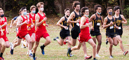 Syosset, New York, USA - 1 November 2020: Start of Hhgh school boys cross country running race with boys wearing face masks on a grass field.