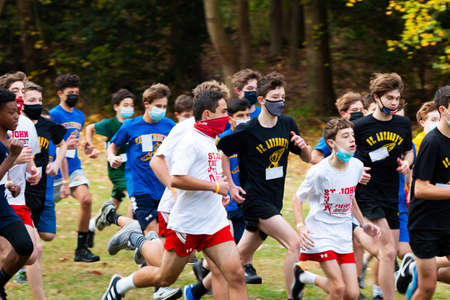 Syosset, New York, USA - 1 November 2020: High school freshmen cross country runners wearing face masks and gaiters while running a race in a park. 新聞圖片