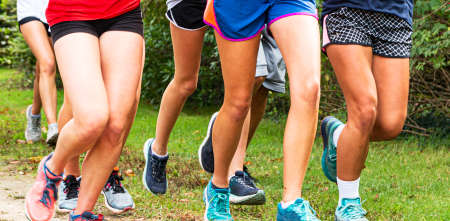 Front view of legs of a high school girls cross country team is running together on a dirt path surrounded by grass in a park.