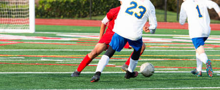 Rear View of a soccer player in a white jersey dribbling the ball around his opponent in a red jersey during a high school game on a green turf field. 版權商用圖片