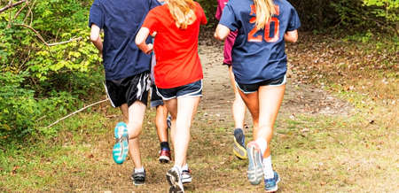 Boys and girls running together during high school cross country practice in a park on a dirt trail.