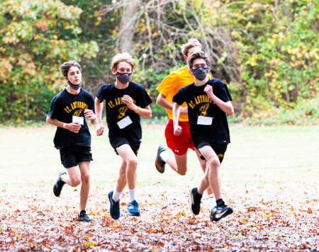 Syosset, New York, USA - 1 November 2020: Boys wearing face masks while running in a cross country race on a field covered in leaves during the coronavirus COVID-19 pandemic. 新聞圖片