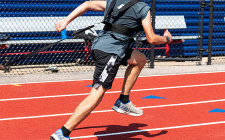 A high school track runner is wearing a harness for pulling a sled with weights on a red track during practice.