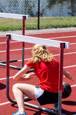 Rear view of a high school girl squating under a hurdle during a strength and agility session at track and field.practice.