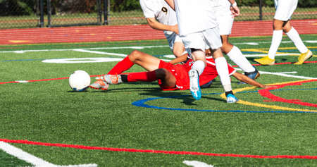A high school boy soccer player in a red uniform slide tackles the ball away from the competition in white uniforms.