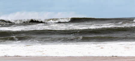 Wide horizontal view of a rough Atlantic Ocean off the coast of Fire Island with the wind blowing to spray of the waves backwards and a blue sky.