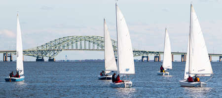 Five two person sailboats in a winter regatta with the Great South Bay Bridge in the background on Long Island New York.