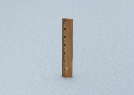 A wooden ruler sticking out of fresh snow fall showing that 5 inches has fallen so far during a blizzard.