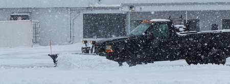 A black truck owned by a private contractor is plowing the snow in the parking lot of a business during a snow storm.