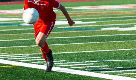 Selective focus on a high school soccer player in a red uniform chasing a high bauncing ball during a match