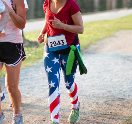 A female runner is wearing American Flag spandex while running a 5K race around a lake.