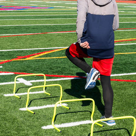 Rear view of a high school track runner is stepping over one foot mini hurdles on a turf field on a cold spring day at track and field practice.
